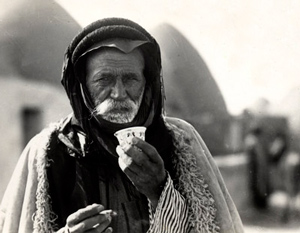A Syrian Bedouin drinks the traditional coffee drink